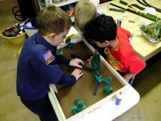 Scouts plan the assembly of a diorama for their Bear badge