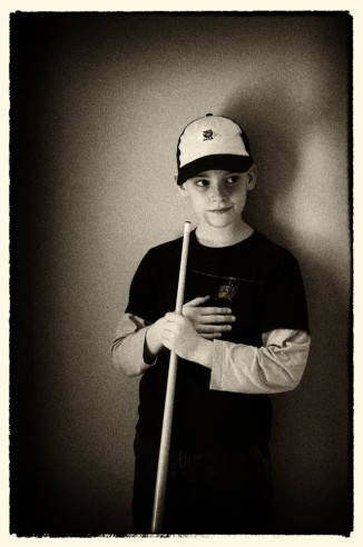 A boy plays his first game of pool...