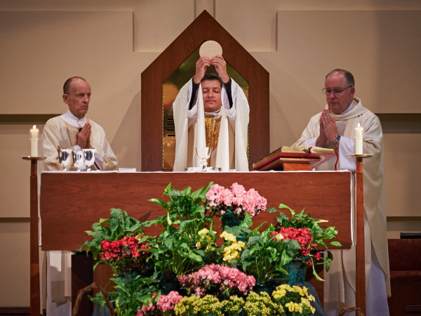 Father Mario consecrates the eucharist