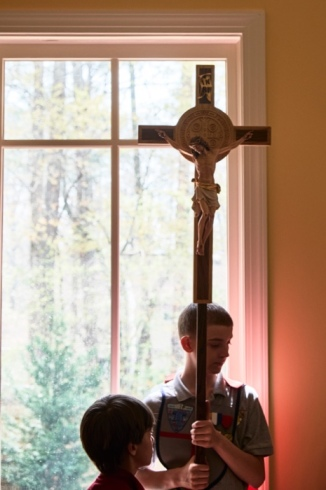 Kalen holds the Cross during the Blue Knight led Stations of the Cross